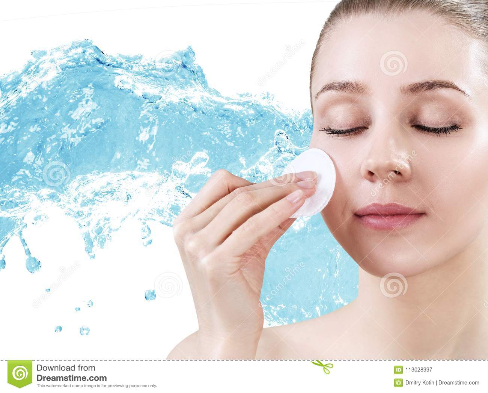 Mujer joven hermosa que limpia su cara con el disco del algodón