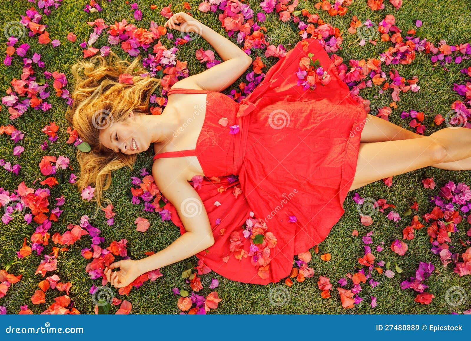 Mujer joven hermosa que miente en flores