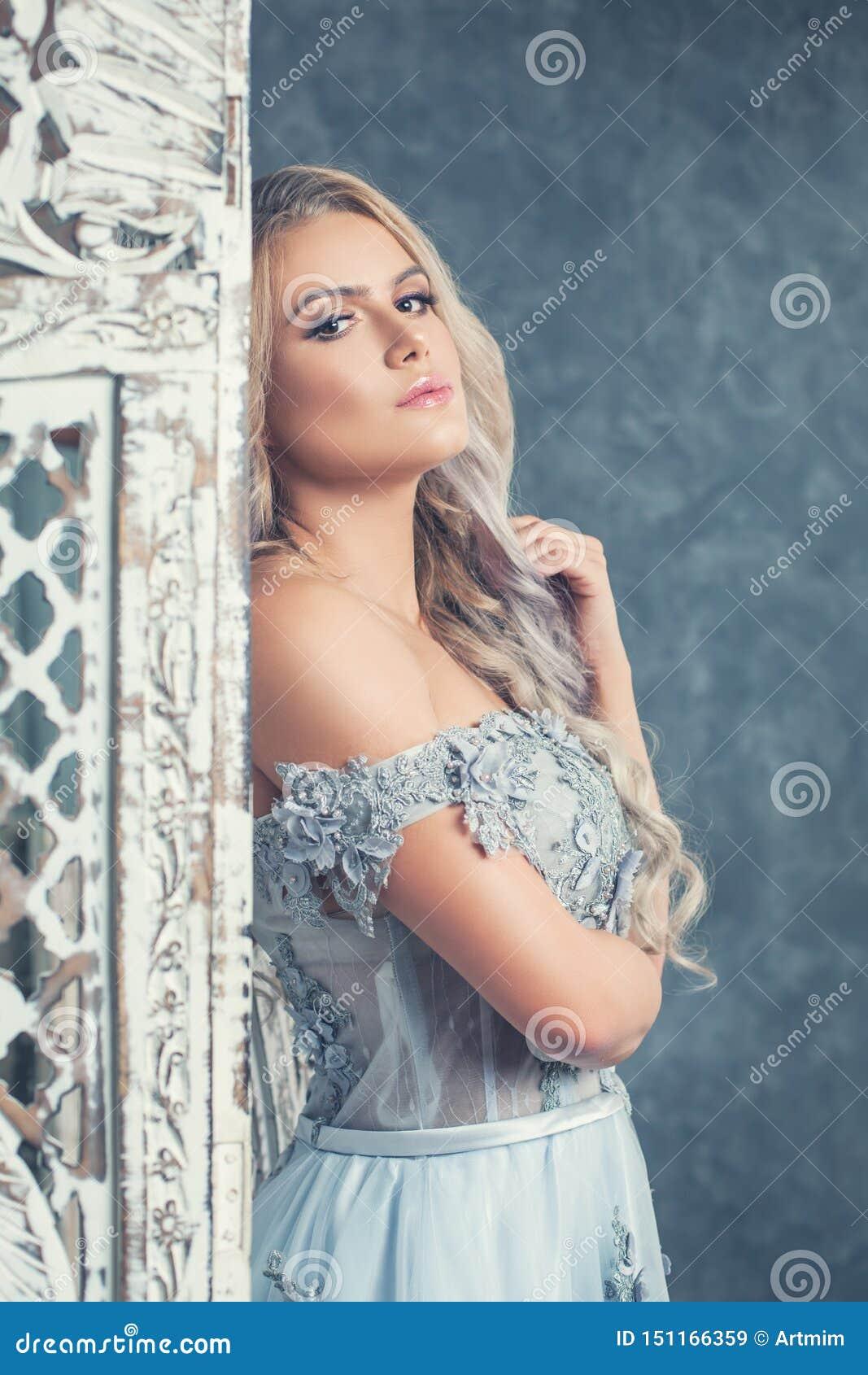 Mujer joven hermosa que plantea el interior lujoso Retrato romántico del vintage de la muchacha rubia