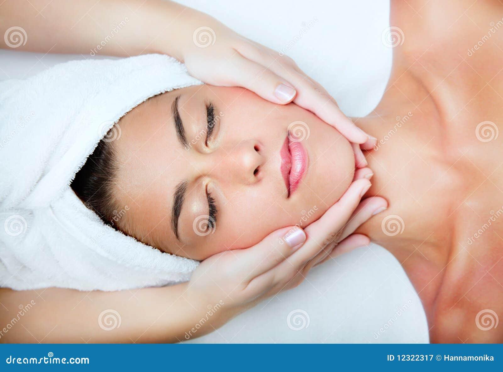 Mujer joven hermosa que recibe masaje facial.