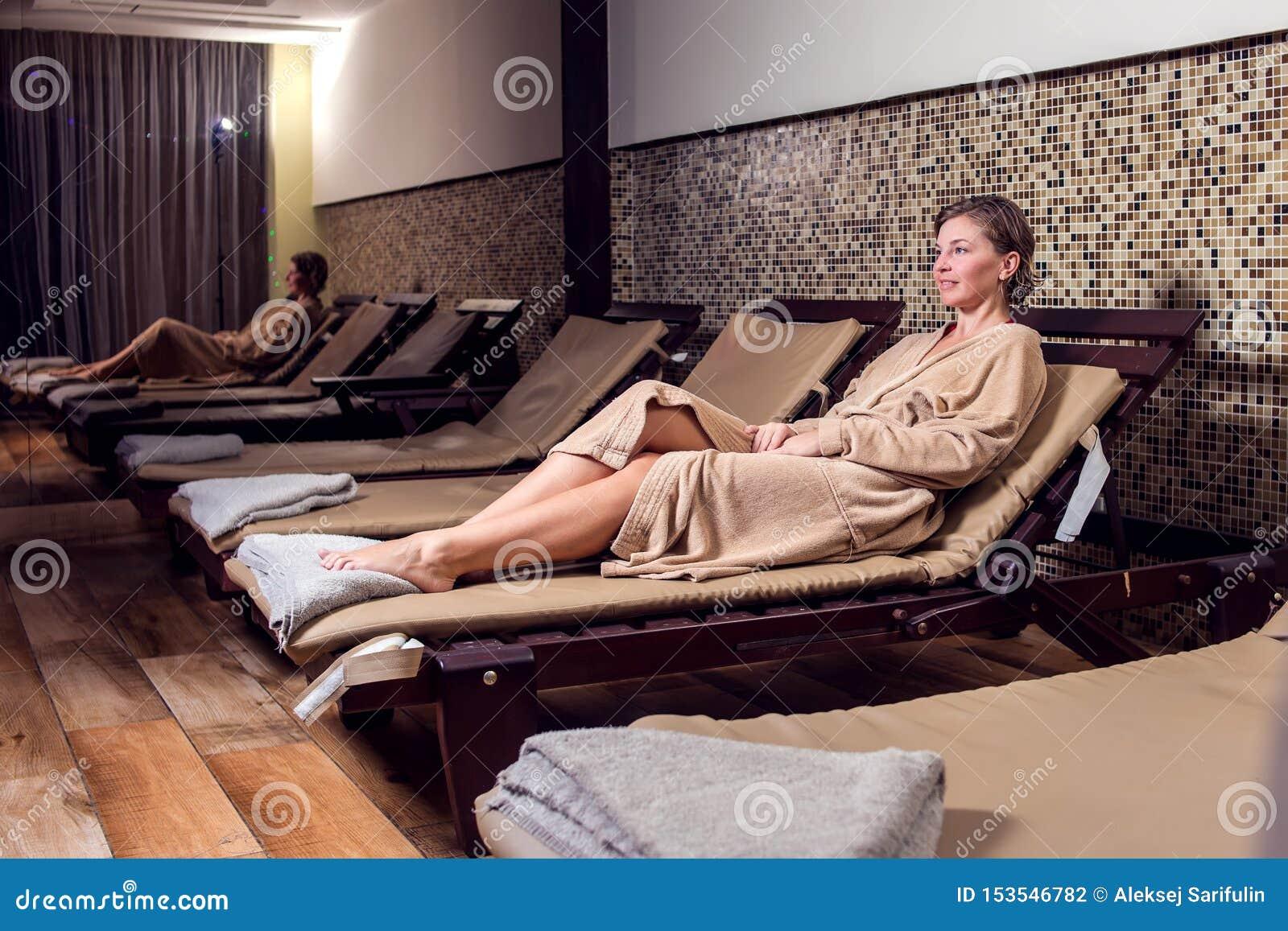 Mujer joven hermosa que relaja y enjoing su tiempo en el salón del balneario
