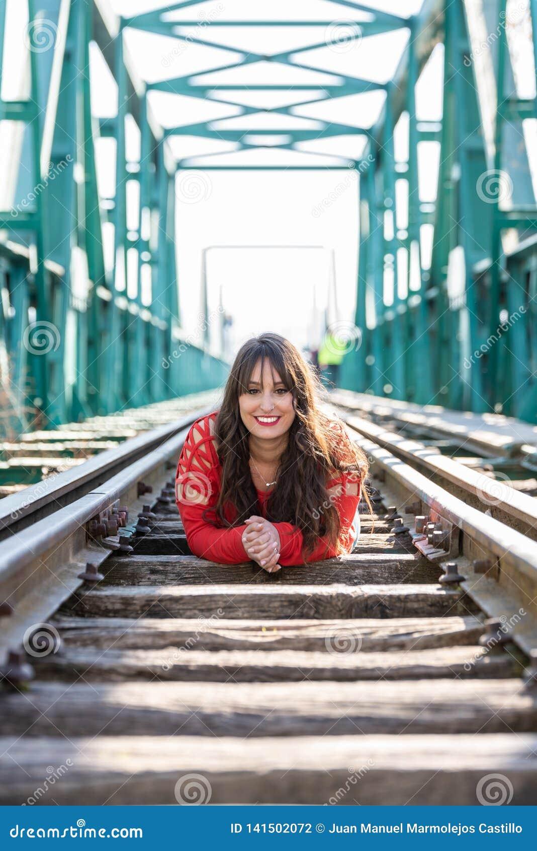 Mujer joven hermosa que se acuesta en las vías del tren