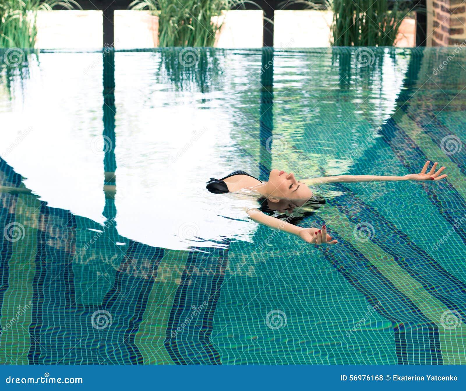 Mujer joven hermosa que se relaja en un balneario