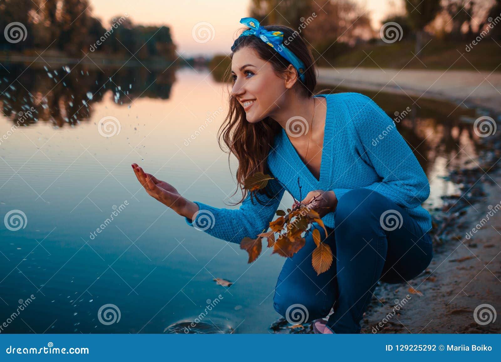 Mujer joven hermosa que se sienta en la orilla del río del otoño que salpica el agua y que lleva a cabo ramas
