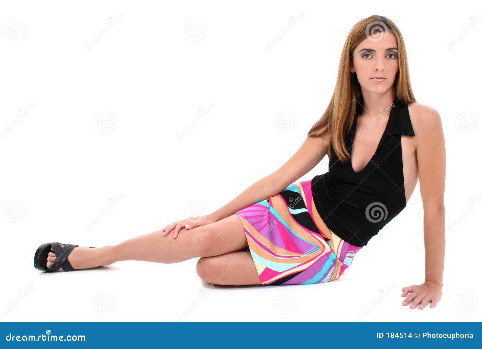 Mujer joven hermosa que se sienta en suelo en alineada del verano