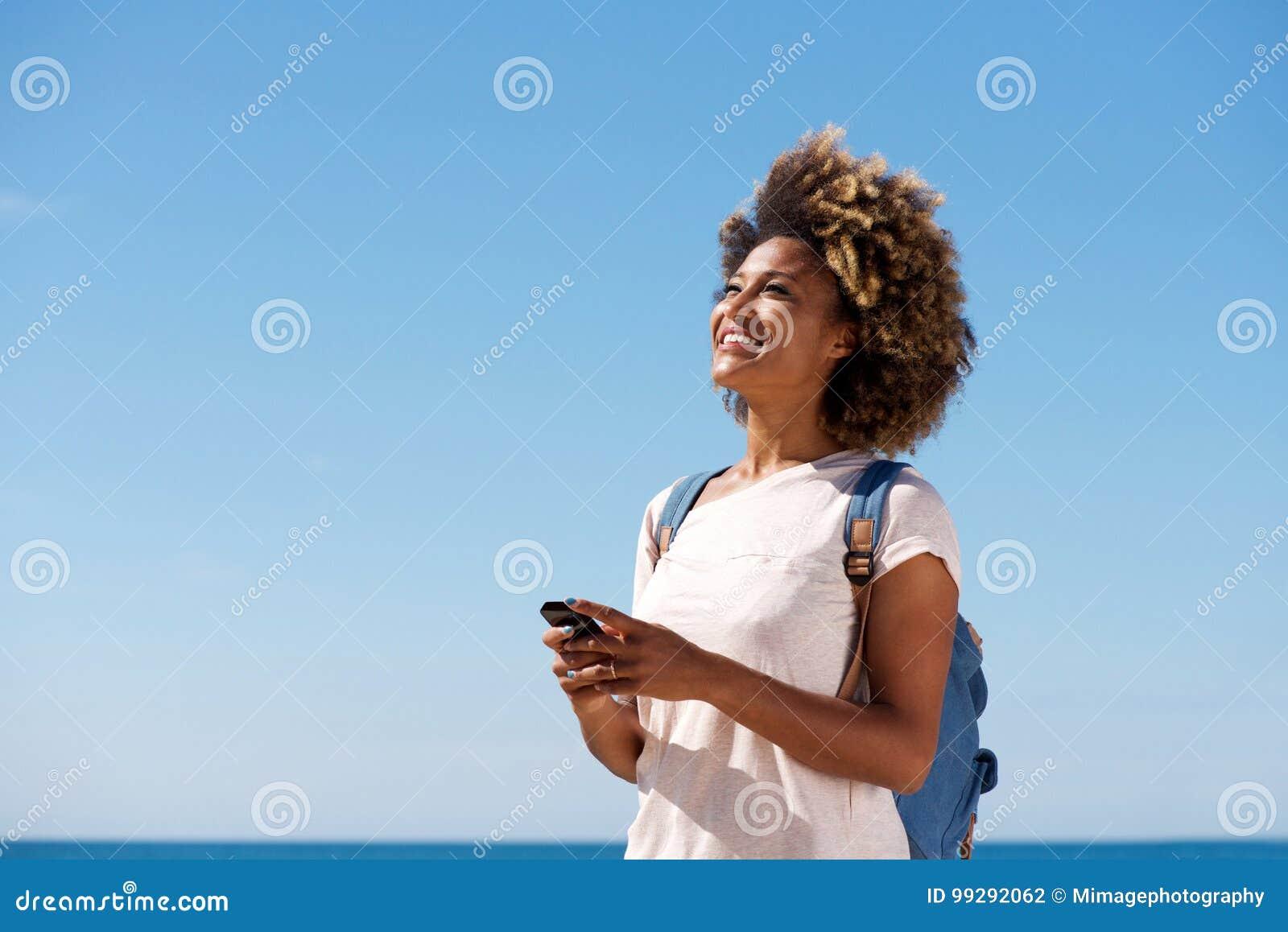Mujer joven hermosa que sonríe contra el cielo