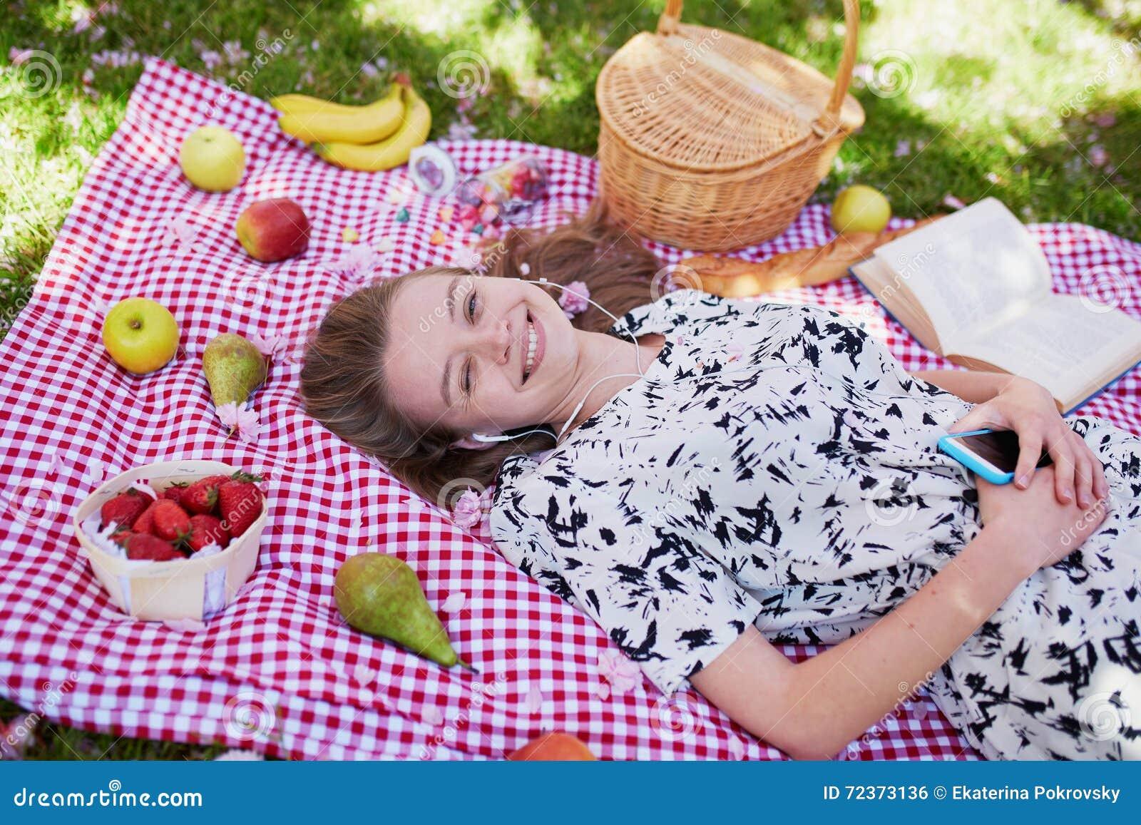 Mujer joven hermosa que tiene comida campestre en parque