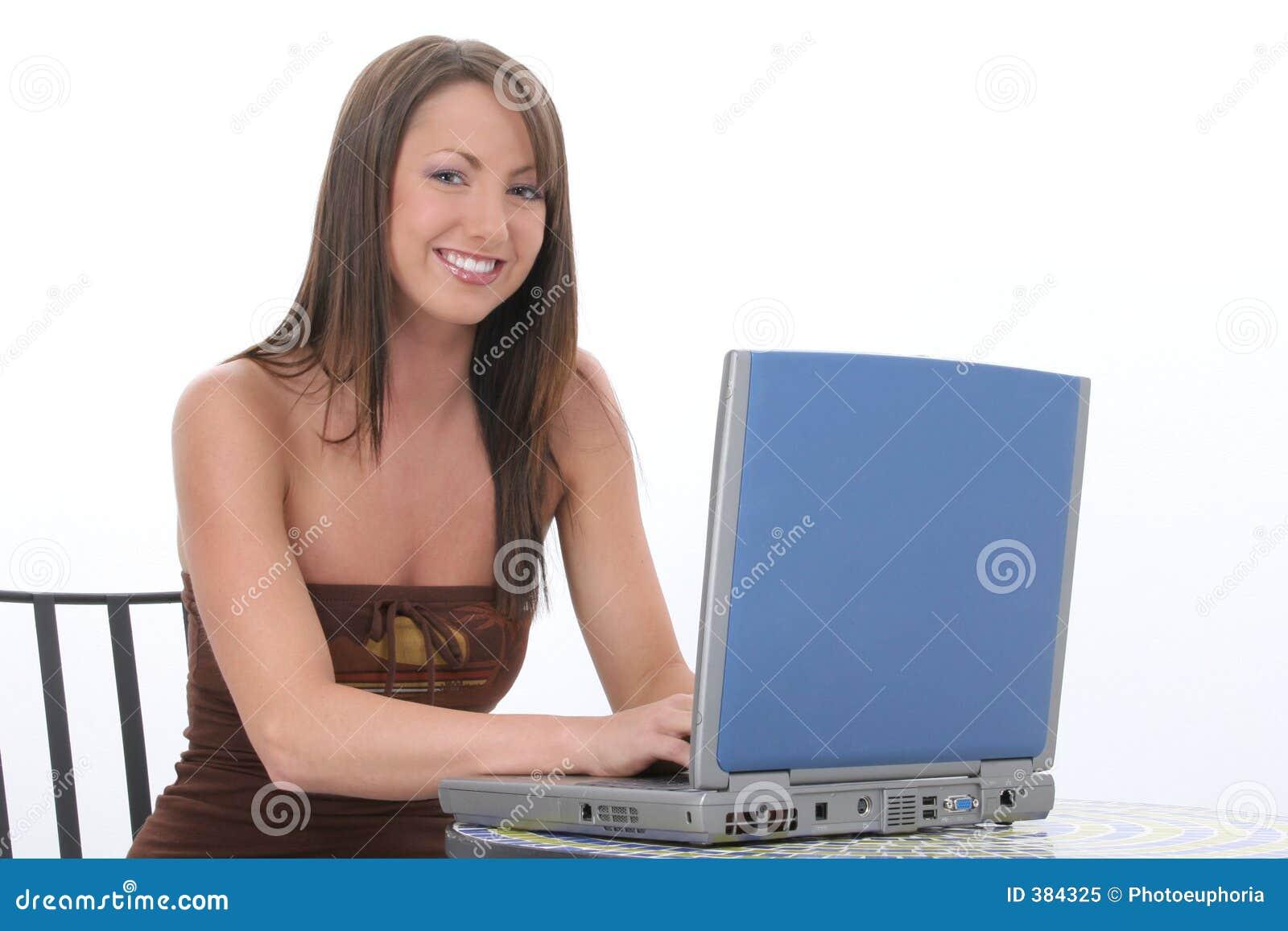 Mujer joven hermosa que trabaja en el ordenador portátil