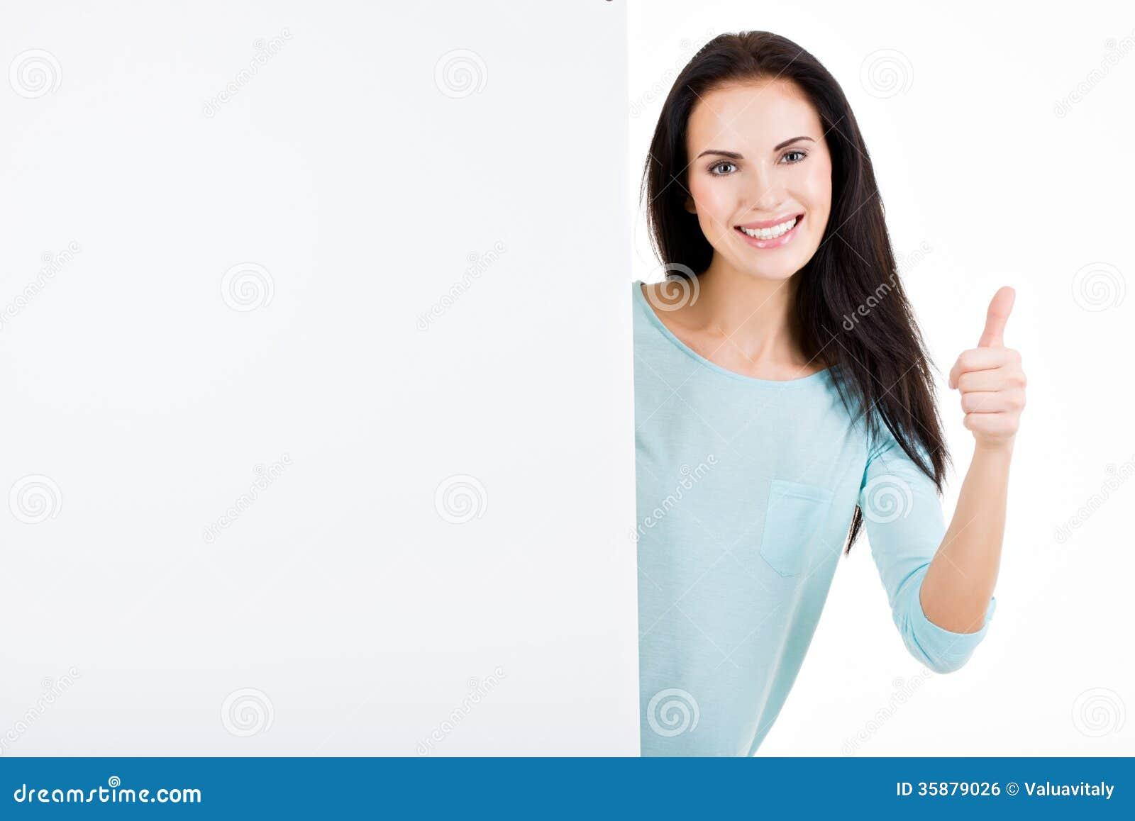 Mujer joven hermosa sonriente feliz que muestra el letrero en blanco