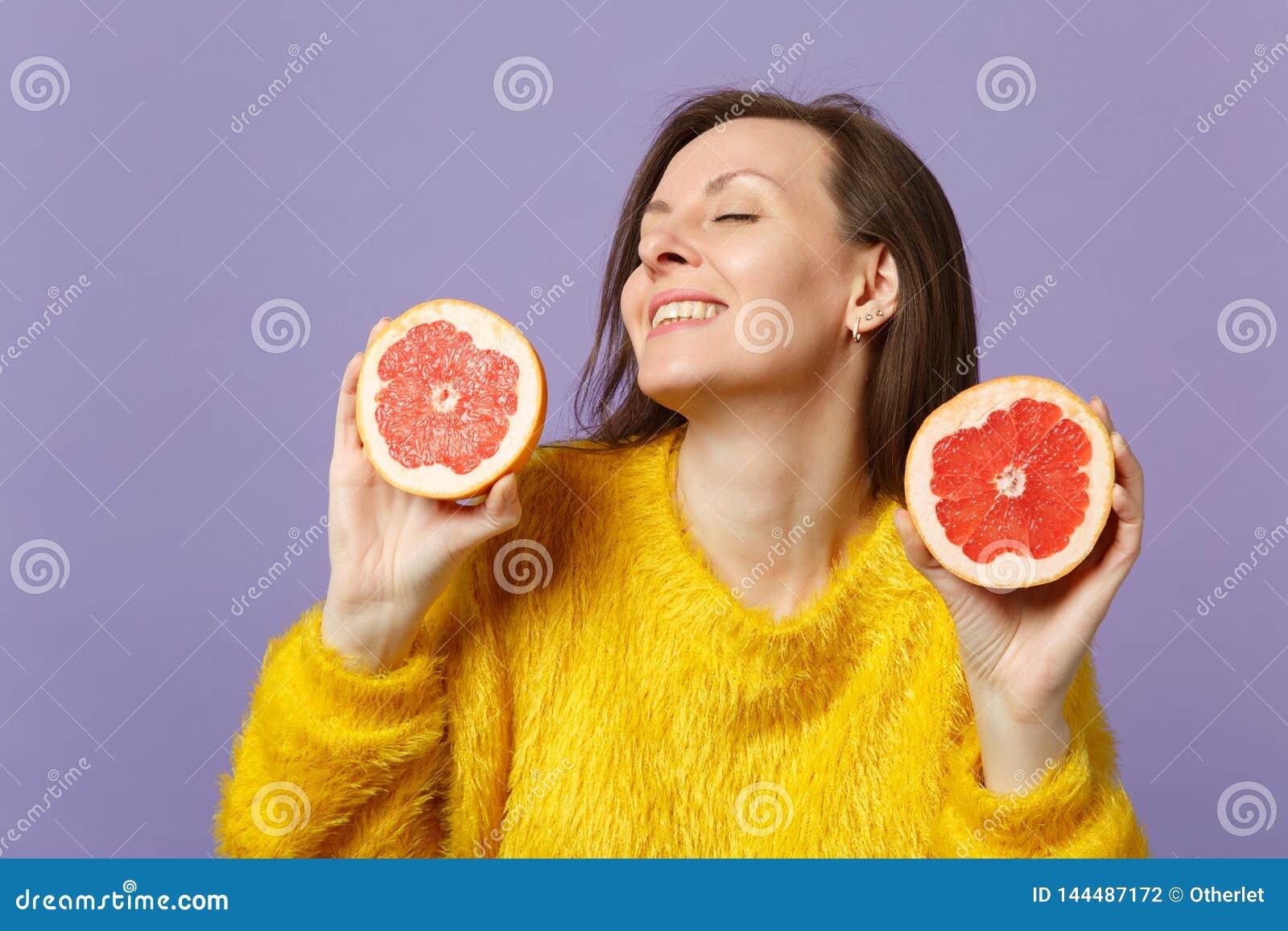 Mujer joven imponente en el suéter de la piel que mantiene ojos cerrados llevando a cabo halfs del pomelo maduro fresco aislado e