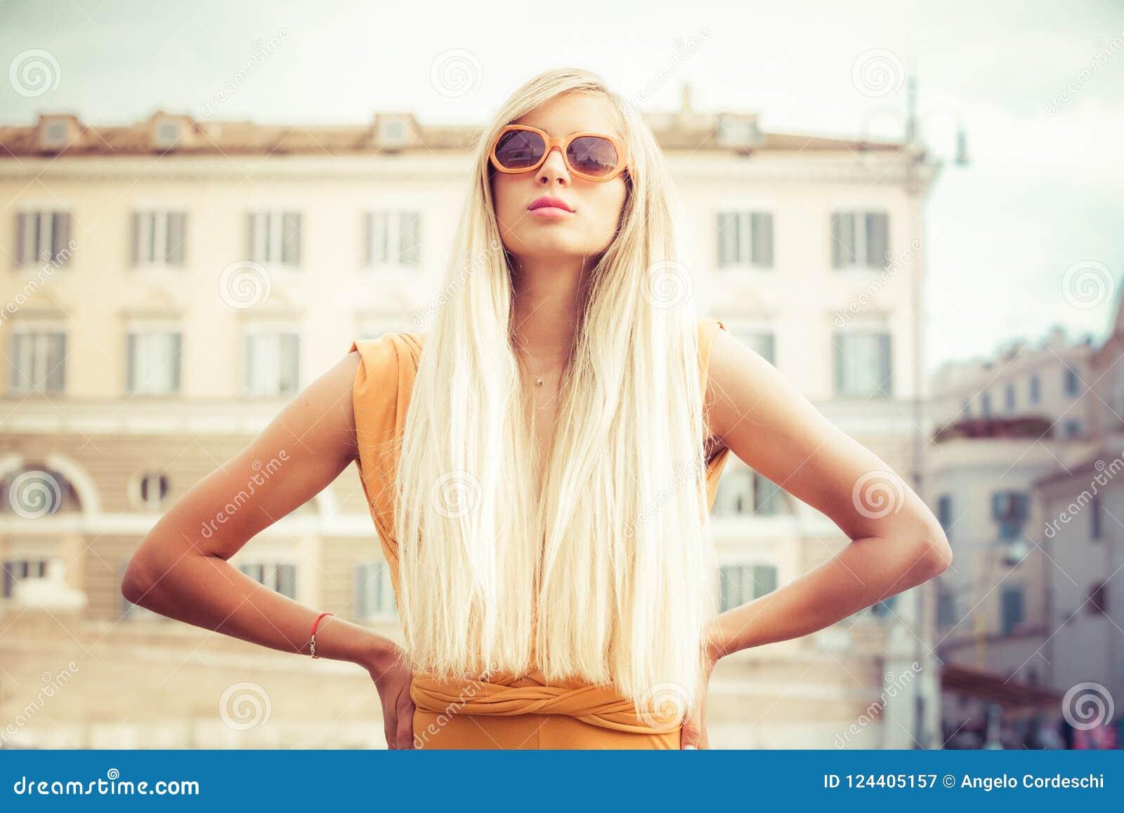 Mujer joven larga elegante del pelo rubio con las gafas de sol en la ciudad