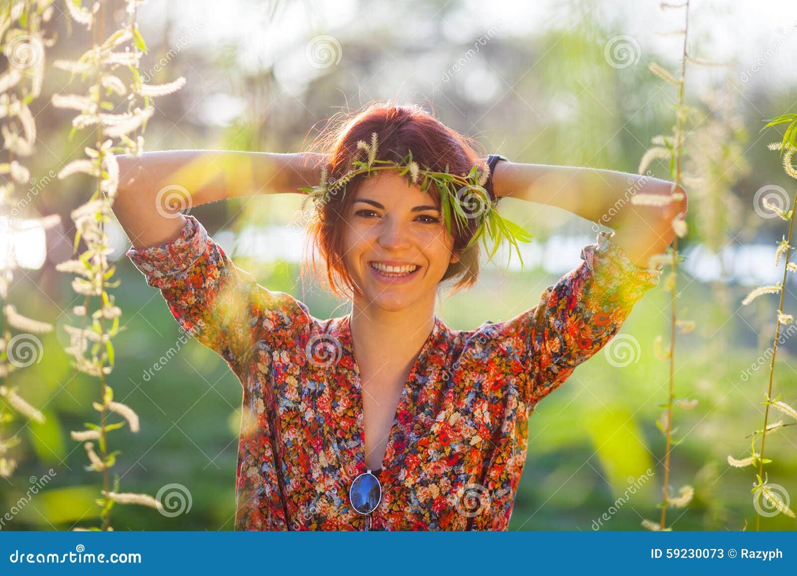 Mujer joven linda con la guirnalda de las ramas