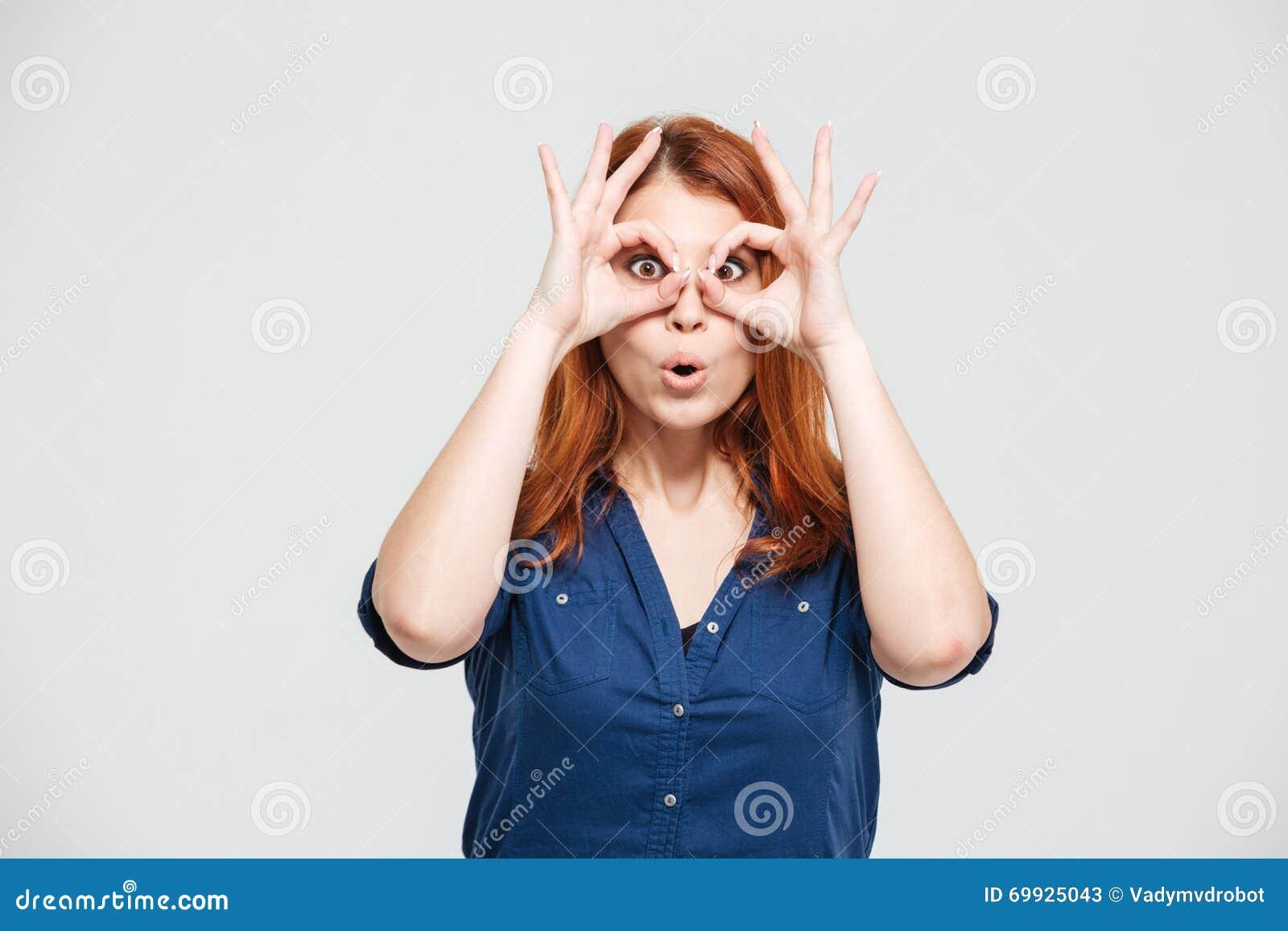 Mujer joven linda divertida que mira los vidrios del throug hechos de fingeres