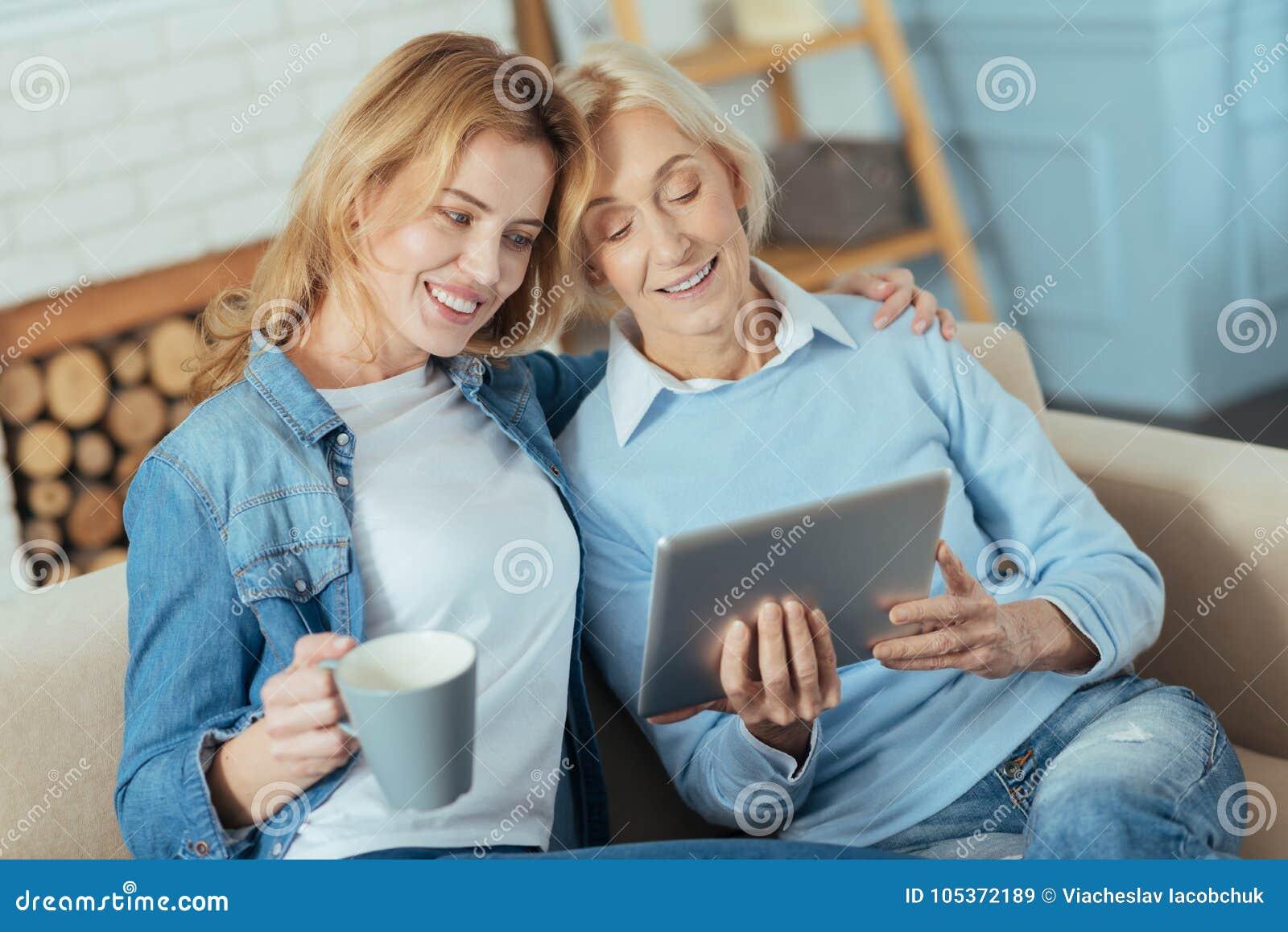 Mujer joven linda que abraza a su abuela mientras que sostiene una taza de té