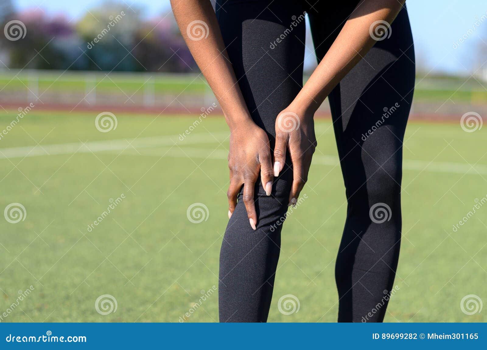 Mujer joven muscular deportiva que agarra su rodilla