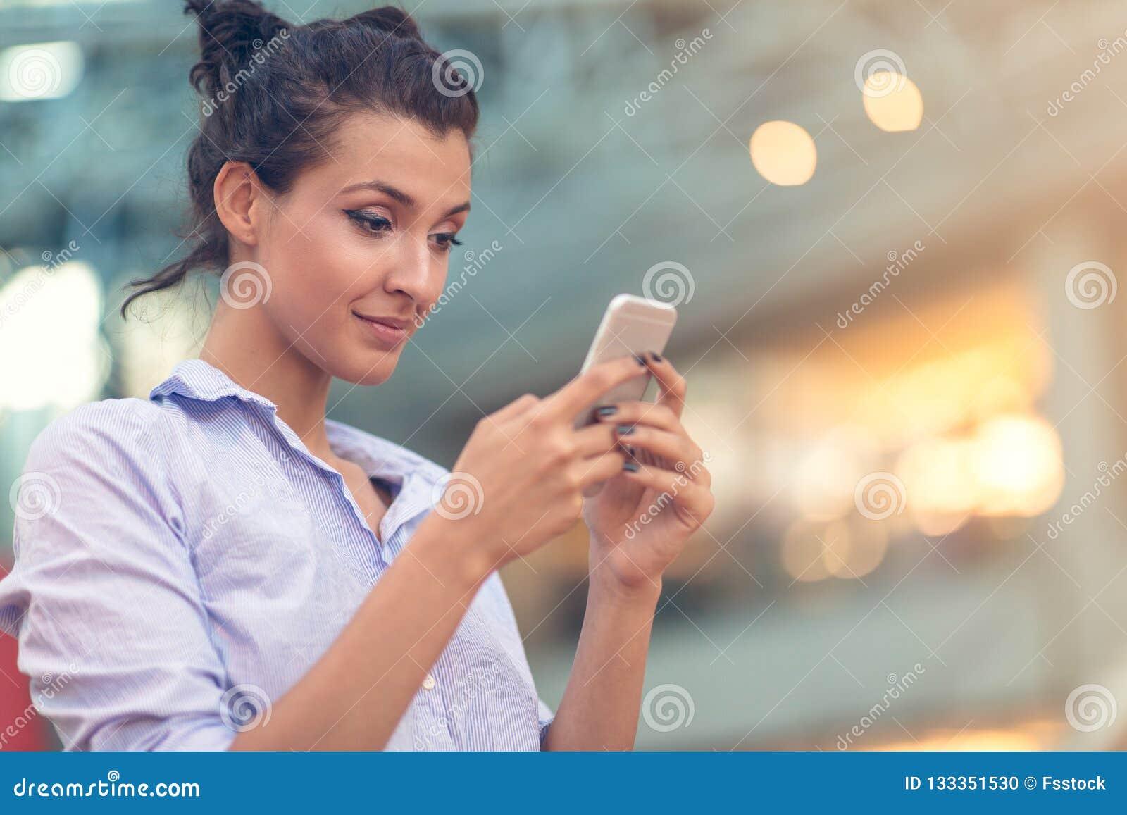 Mujer joven ocupada con la llamada, charlando en el retrato de la vista lateral del teléfono celular