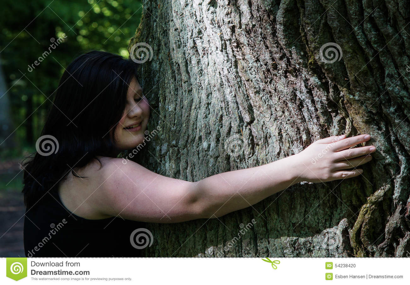 Mujer joven que abraza un árbol