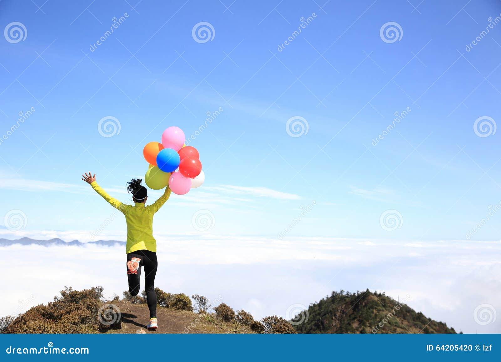 Mujer joven que anima funcionada con con los globos