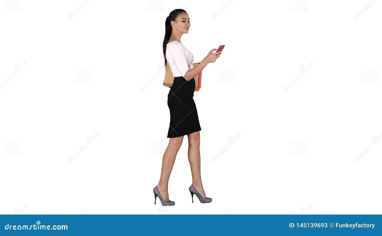 Mujer joven que camina con los bolsos de compras que hablan en el tel?fono m?vil en el fondo blanco