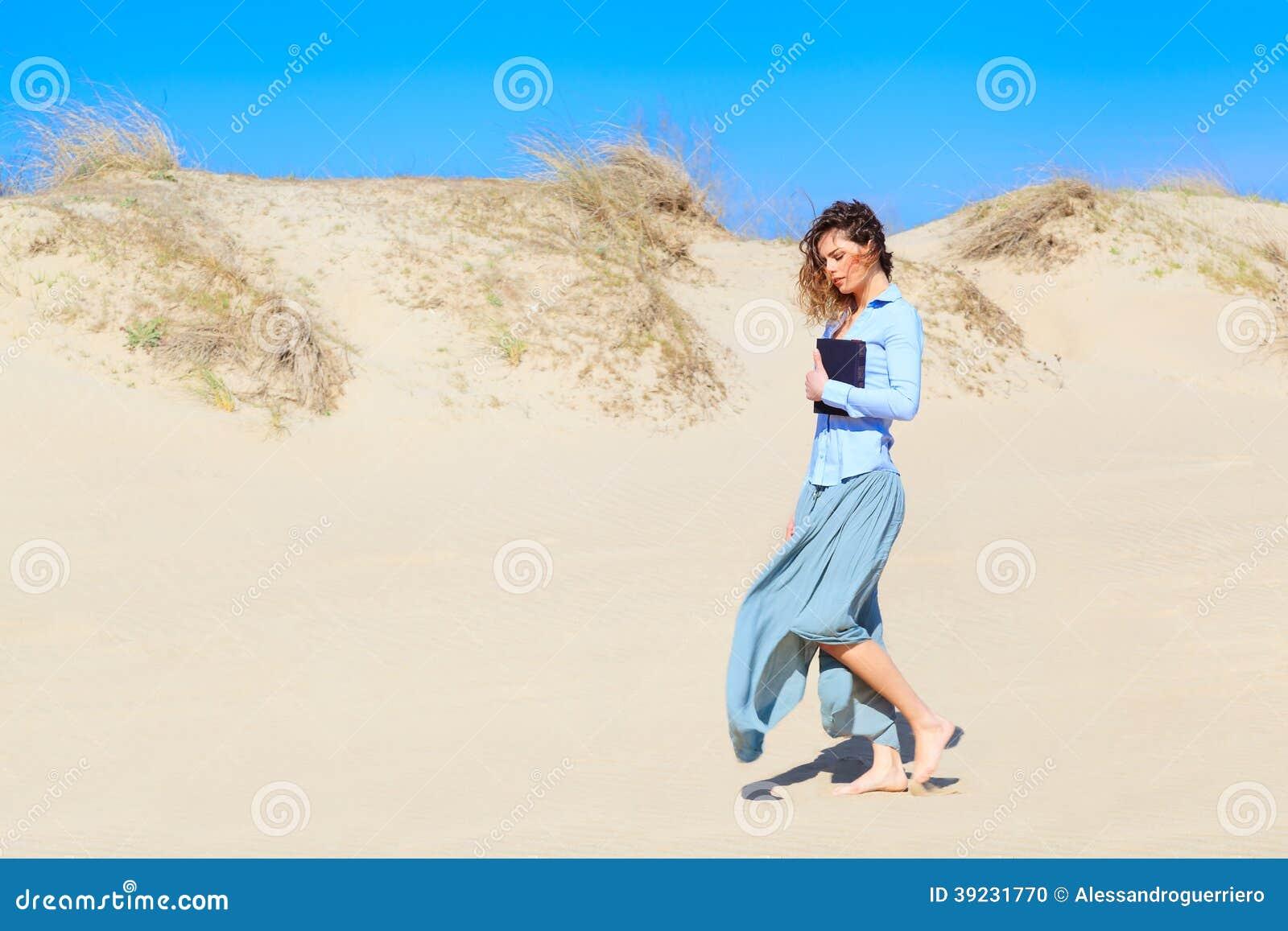 Mujer joven que camina en la playa