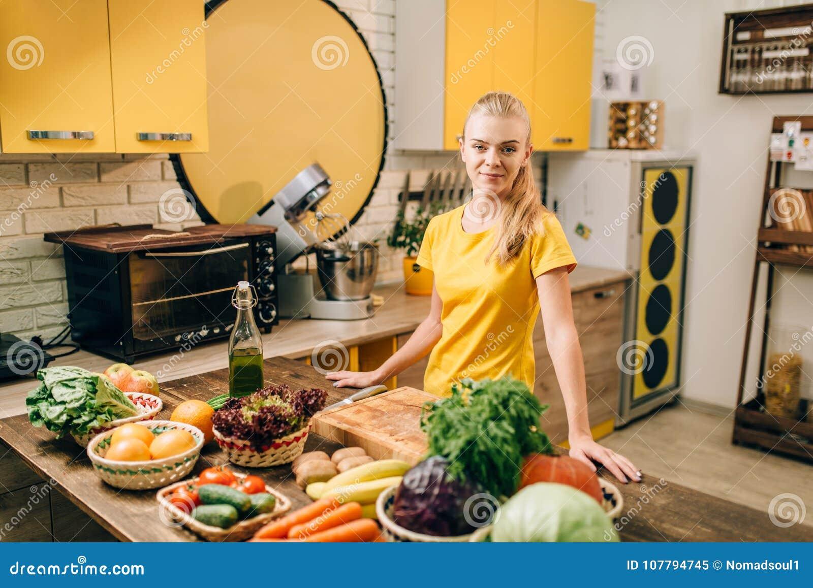 Mujer joven que cocina en la cocina, comida sana