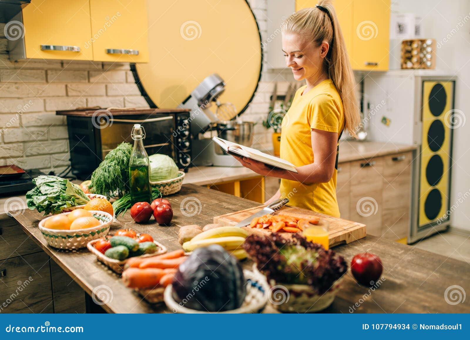 Mujer joven que cocina en recetas, comida sana del eco