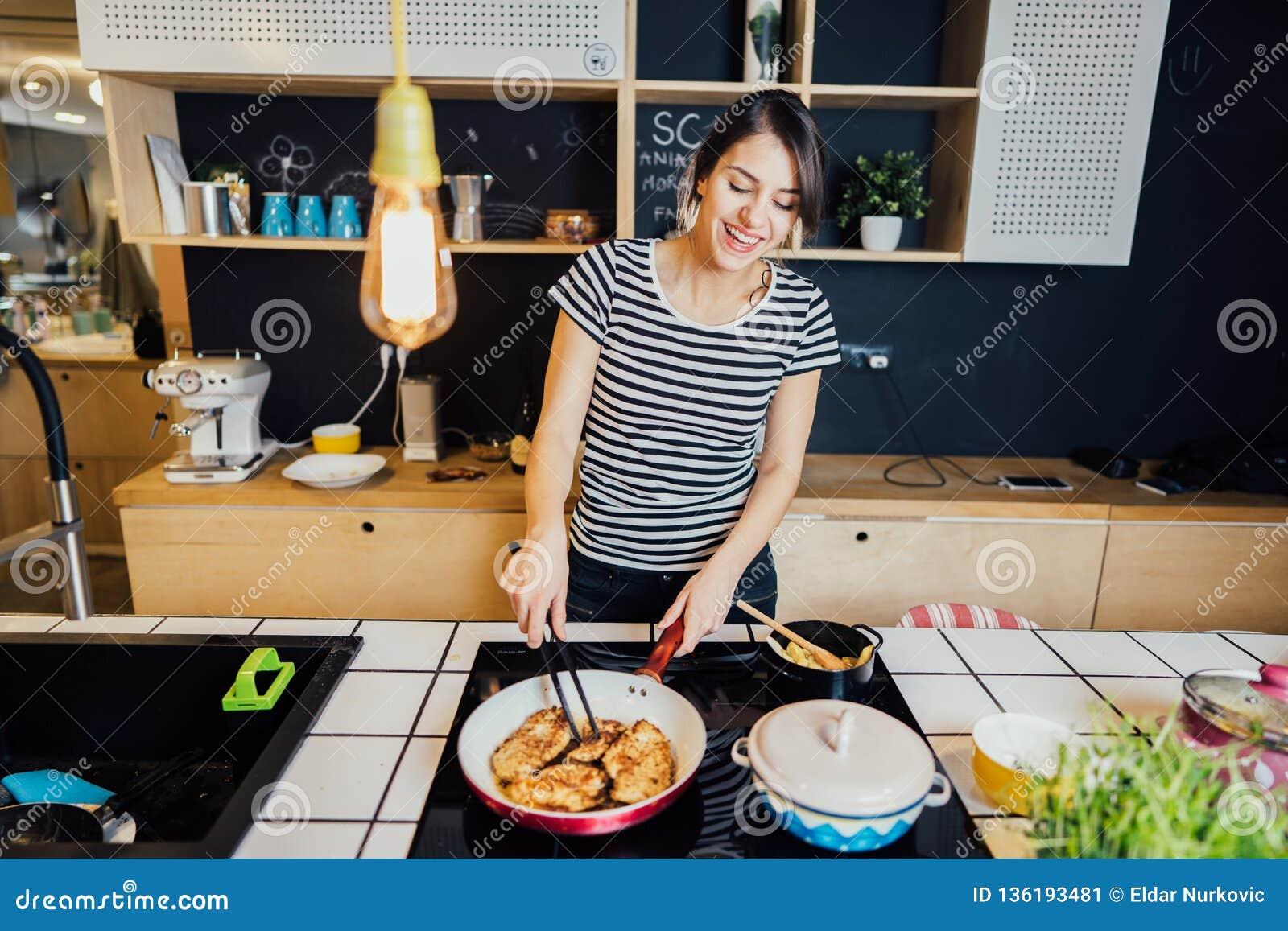 Mujer joven que cocina una comida sana en la cocina casera Fabricación de la cena en el avellanador de la inducción de la isla de