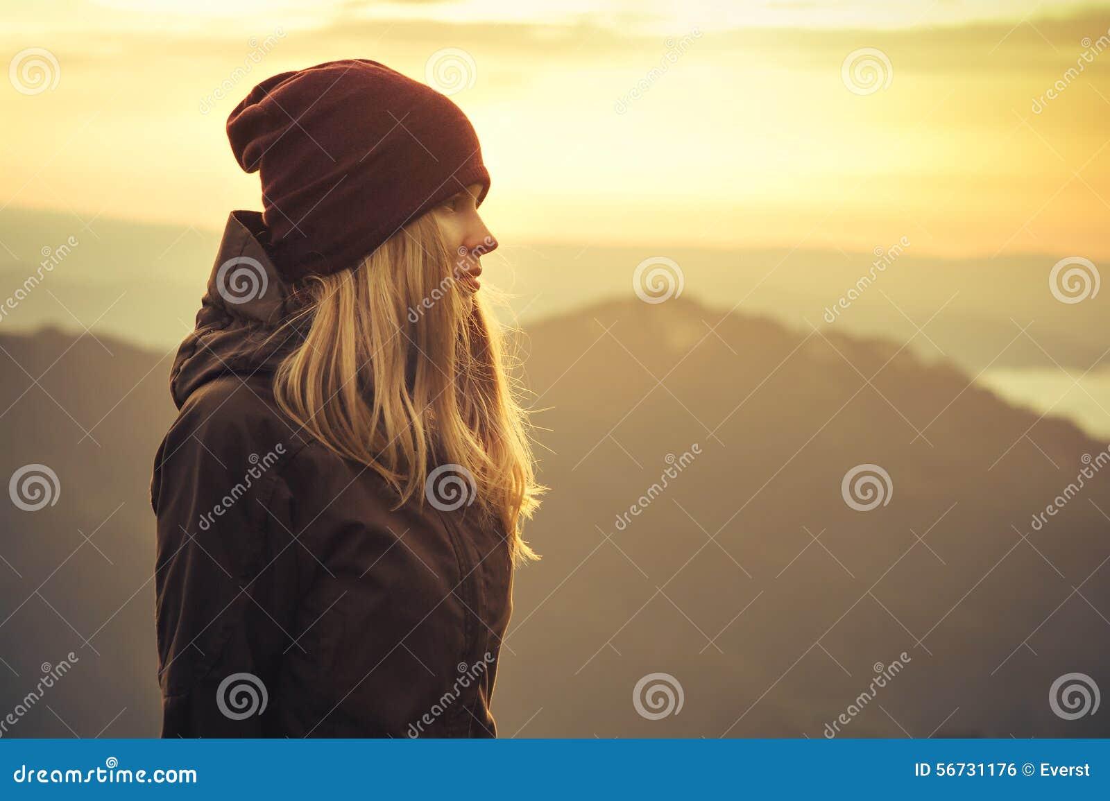 Mujer joven que coloca al aire libre solo