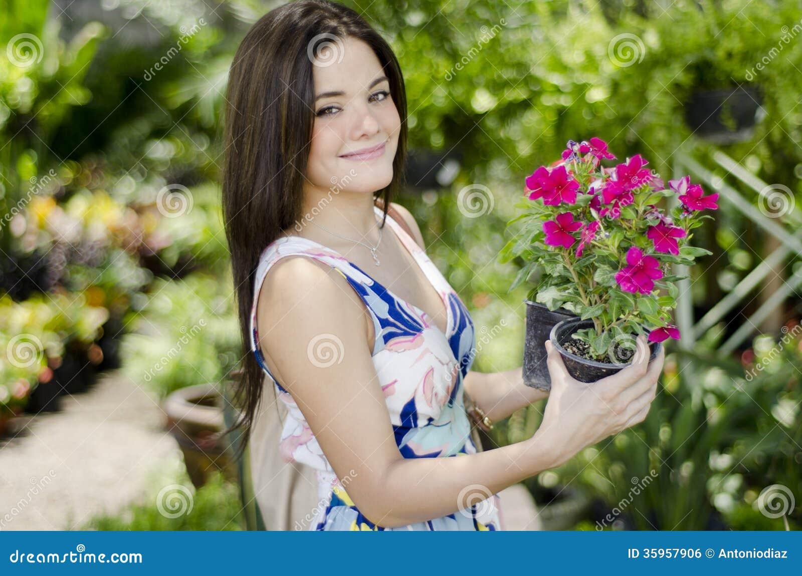 Mujer joven que compra algunas plantas