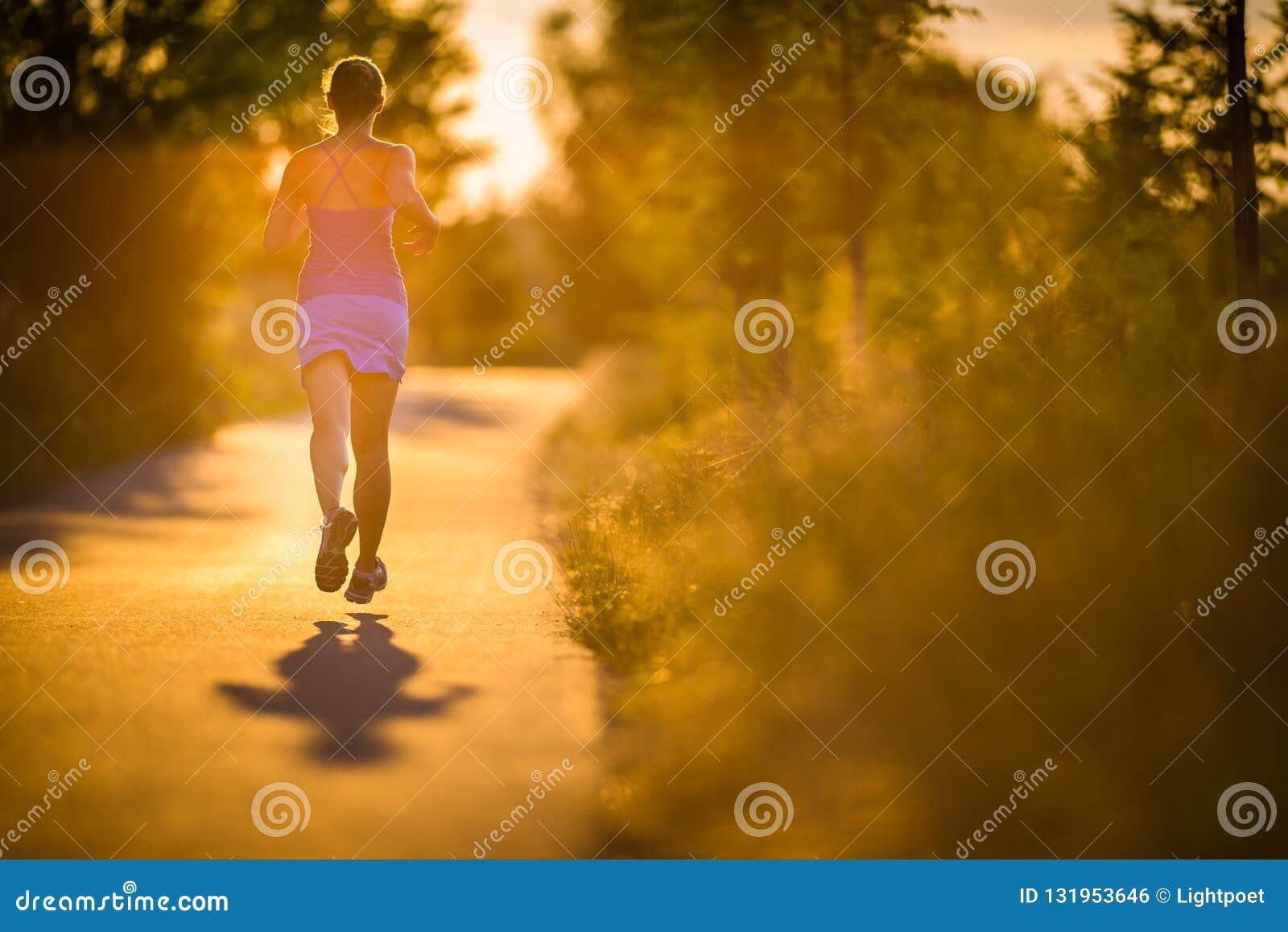 Mujer joven que corre al aire libre en evenis soleados preciosos de un verano