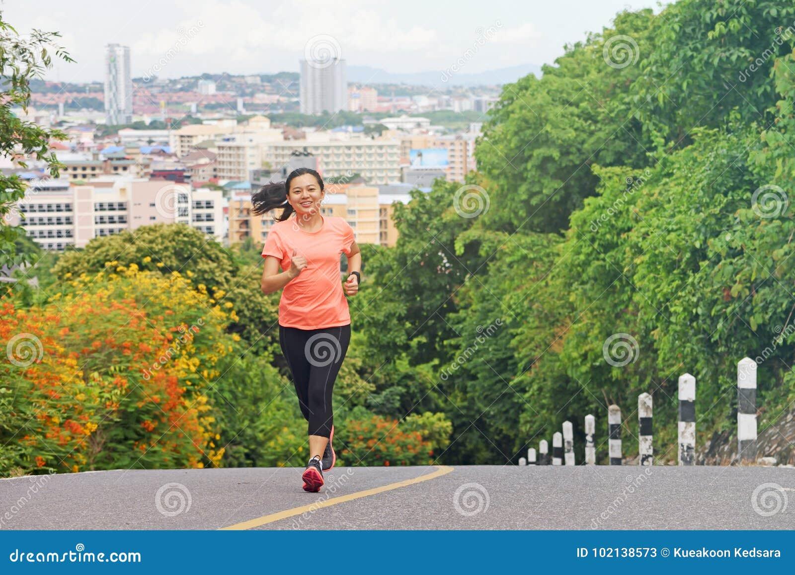 Mujer joven que corre al aire libre en parque