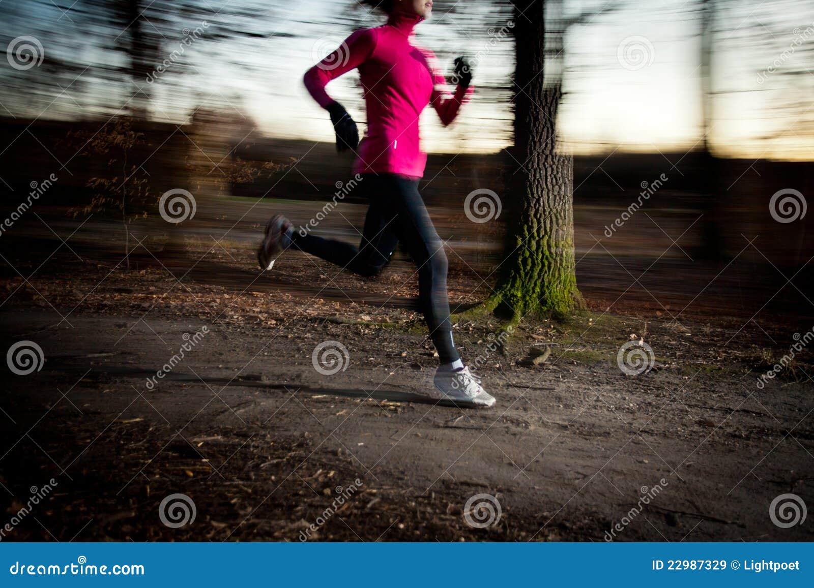 Mujer joven que corre al aire libre en un parque de la ciudad