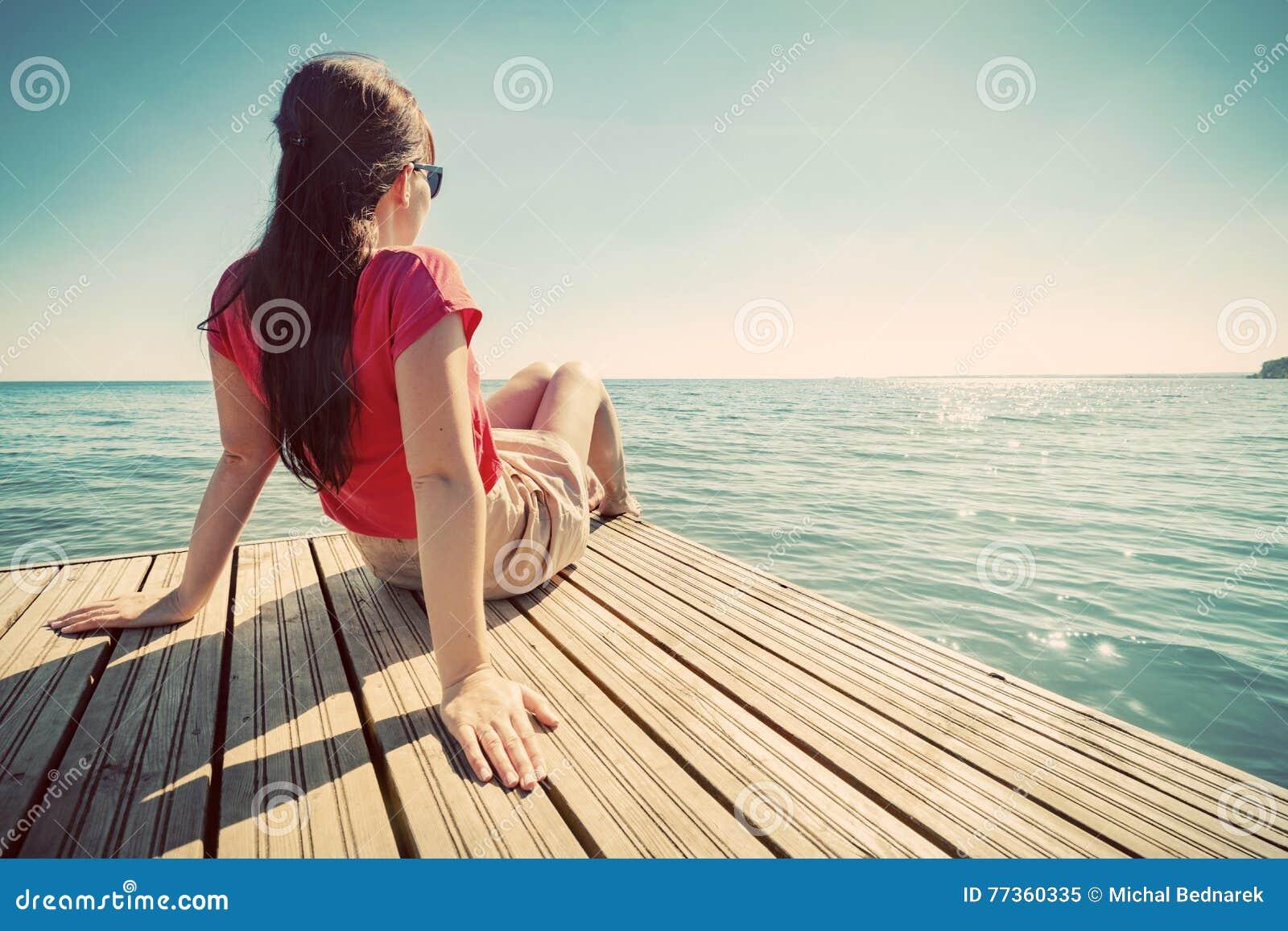 Mujer joven que descansa sobre el embarcadero que mira el mar tranquilo en día de verano soleado