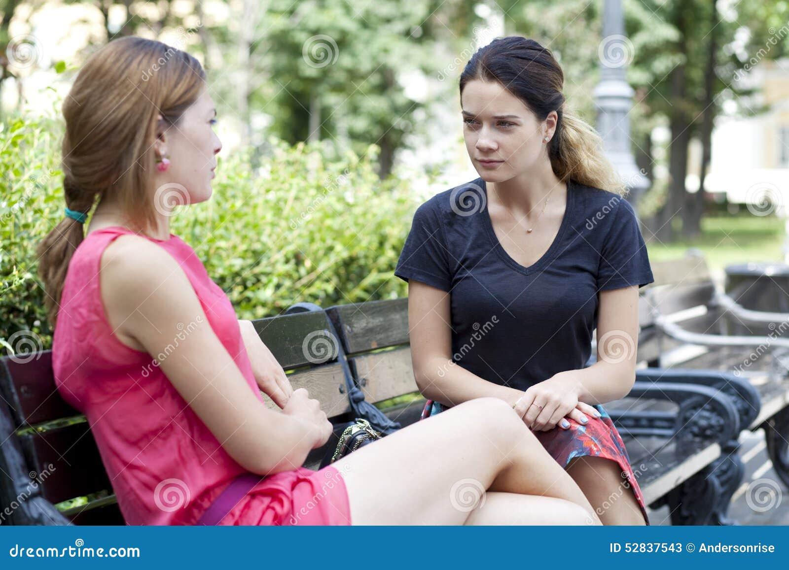 Mujer joven que descansa sobre un banco en el parque