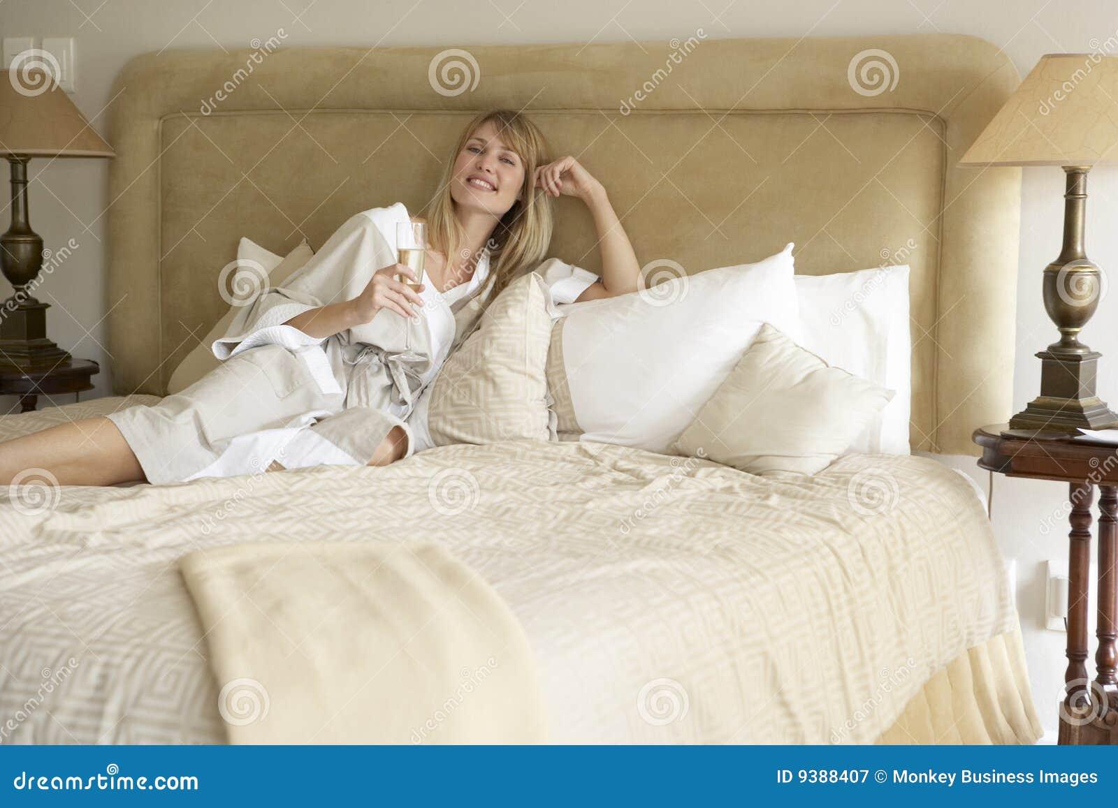 Mujer joven que disfruta de Champán en dormitorio