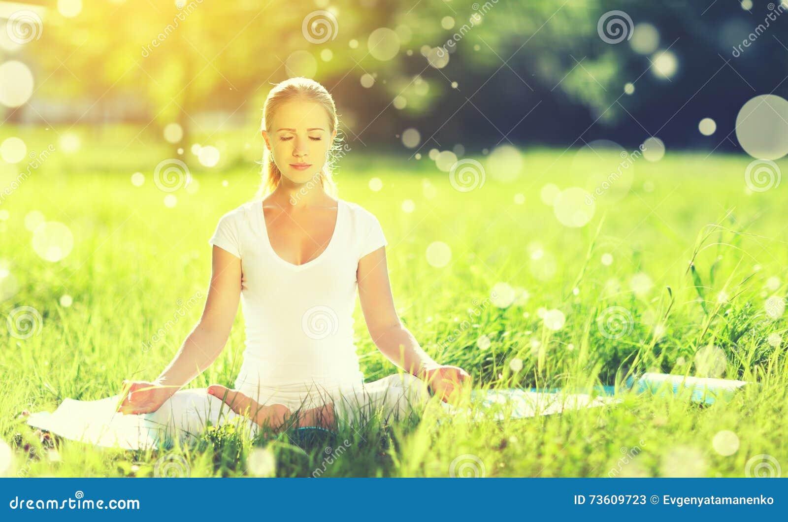 Mujer joven que disfruta de la meditación y de la yoga en hierba verde en summe