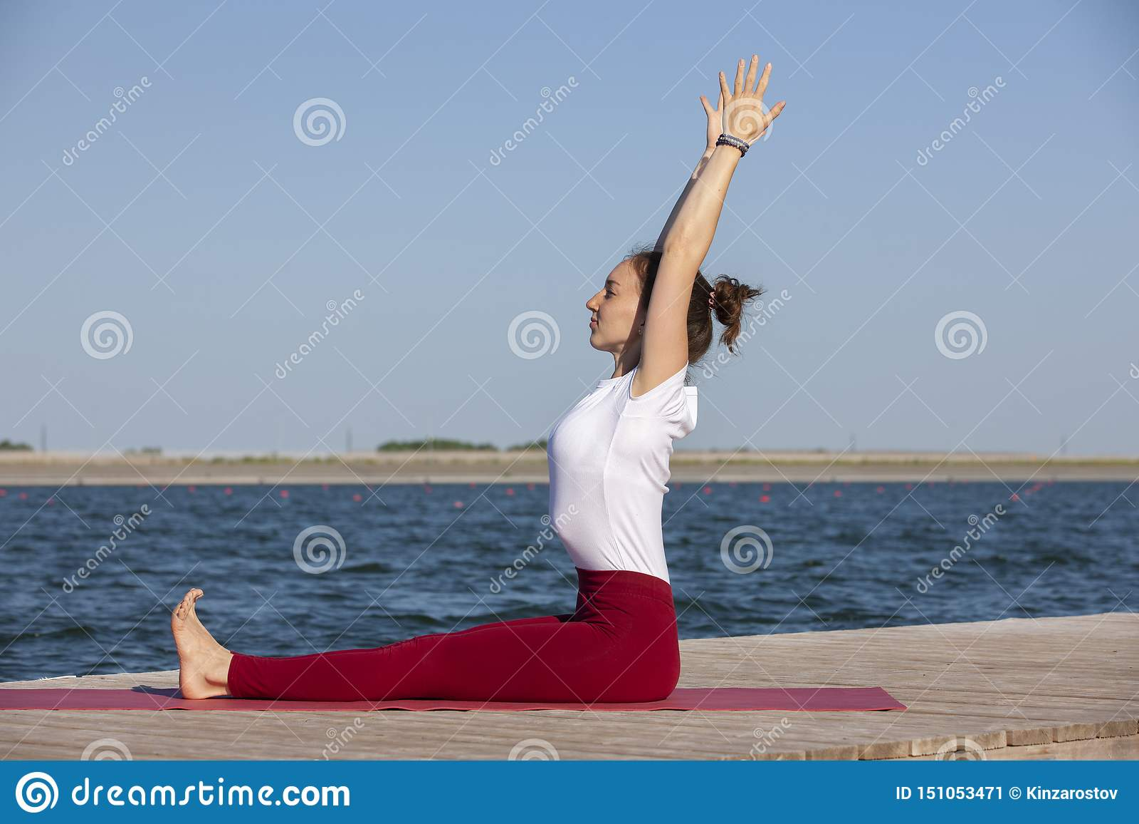 Mujer joven que ejercita actitud de la yoga por la orilla en la puesta del sol, muchacha del lago en actitud de la yoga del heads