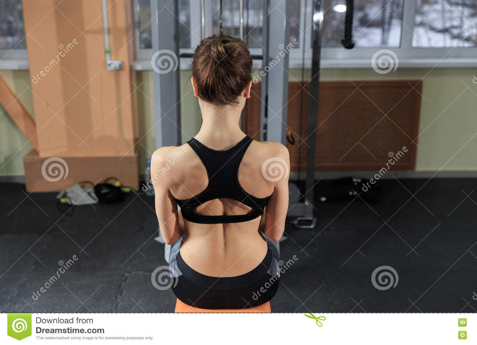 Mujer joven que ejercita detrás en la máquina en el gimnasio y que dobla los músculos - modelo atlético muscular de la aptitud de