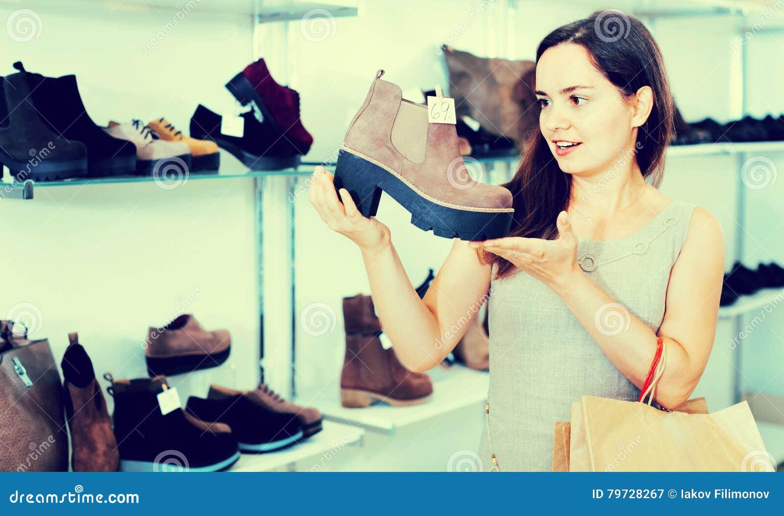 Mujer joven que elige botas de la caída en tienda de zapatos