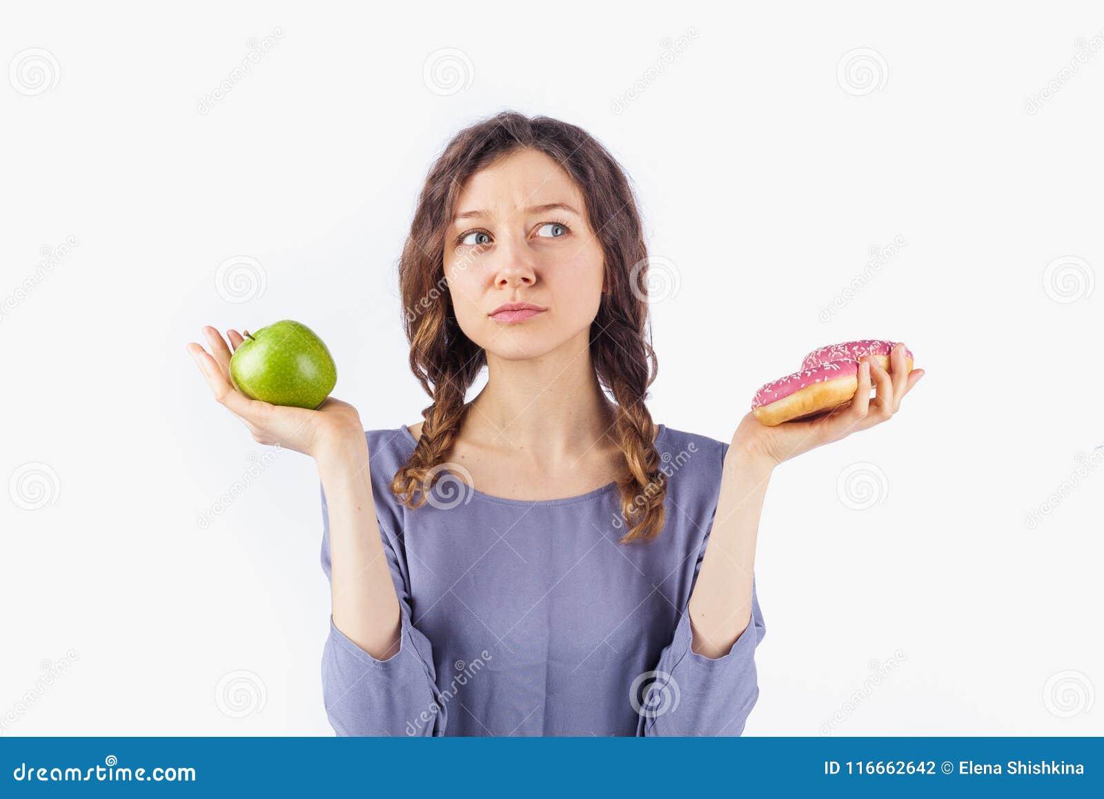 Mujer joven que elige entre una manzana y un buñuelo El concepto de una dieta sana y de dieta