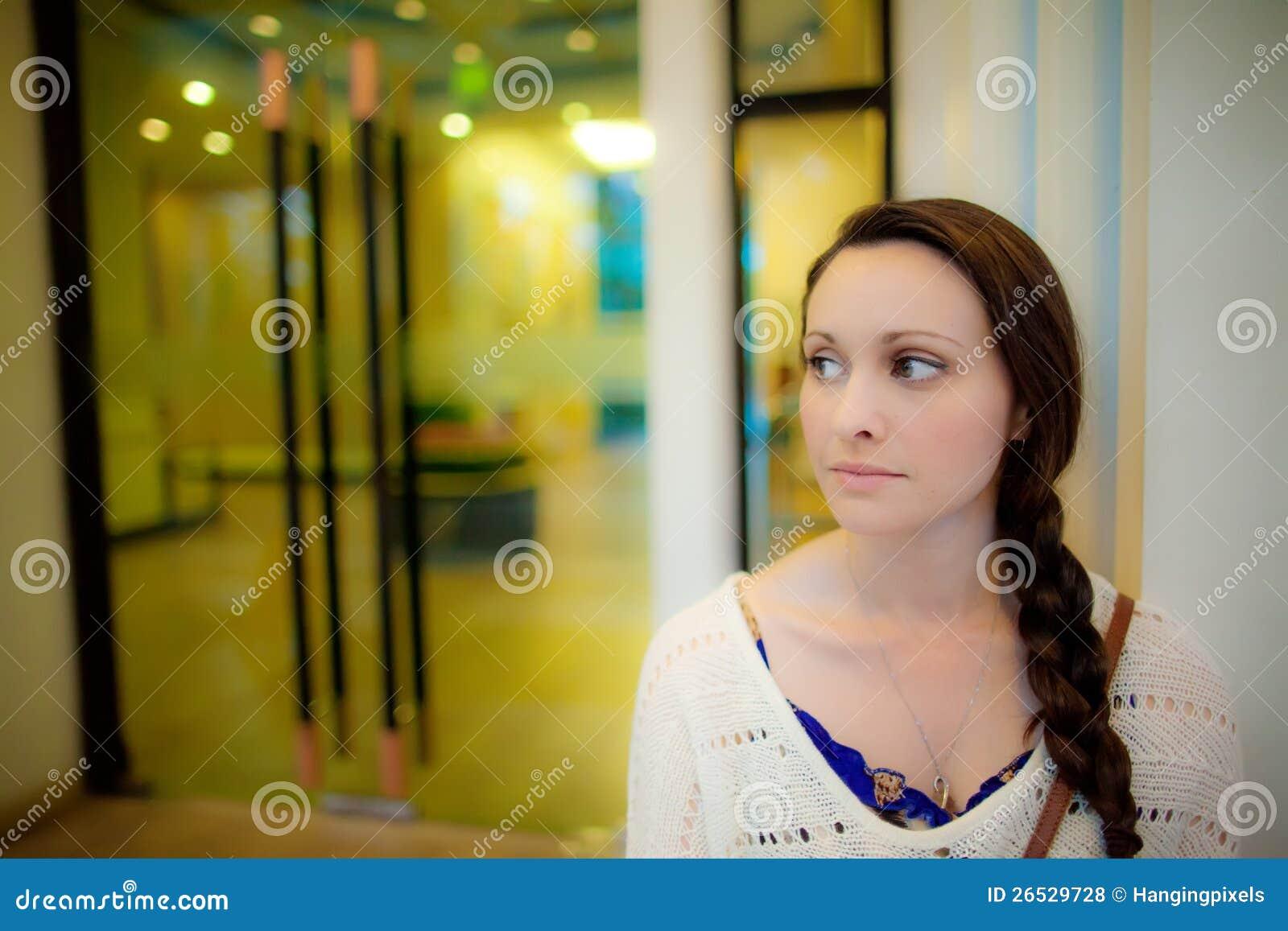 Mujer joven que espera delante de puerta del hotel en Asia