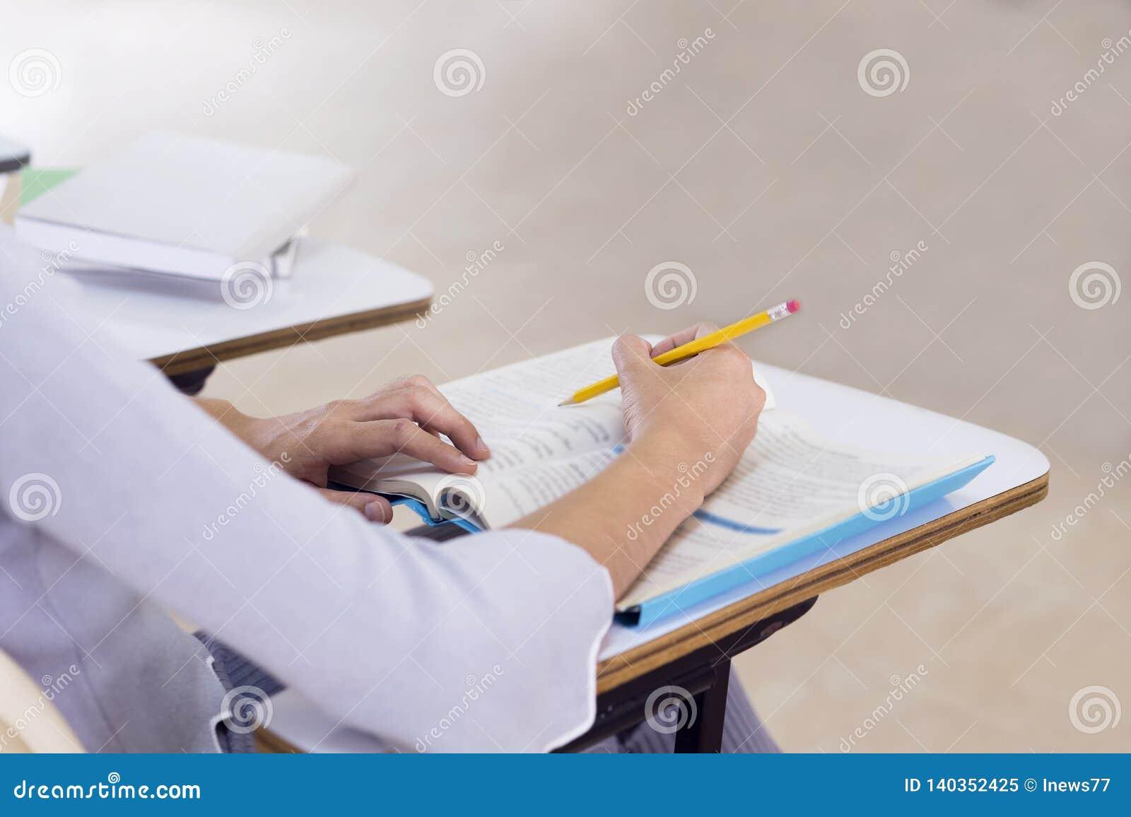 Mujer joven que estudia para una prueba, manos del estudiante que escriben en libro en la sala de clase Aprendizaje y educación,