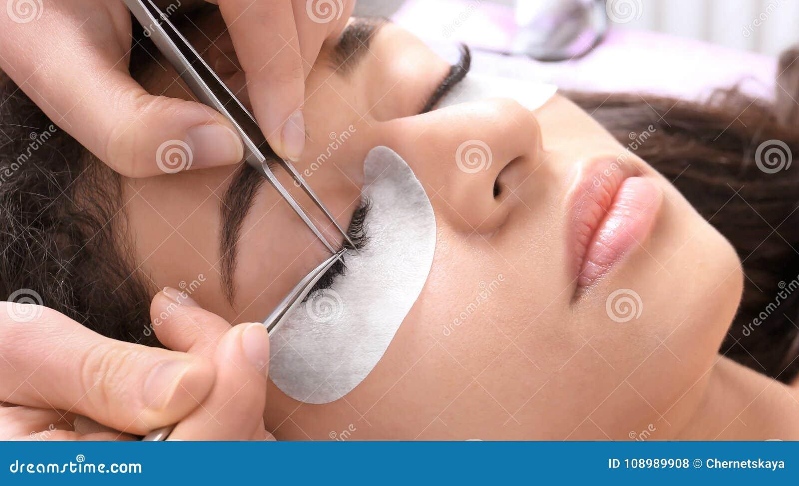 Mujer joven que experimenta procedimiento de las extensiones de la pestaña,