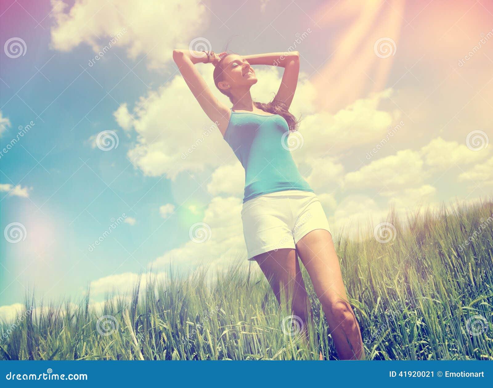 Mujer joven que goza del sol caliente del verano
