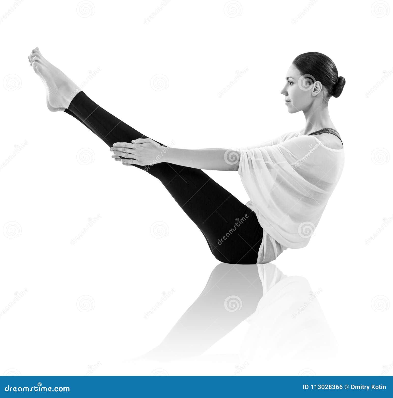Mujer joven que hace ejercicio de la yoga en el piso