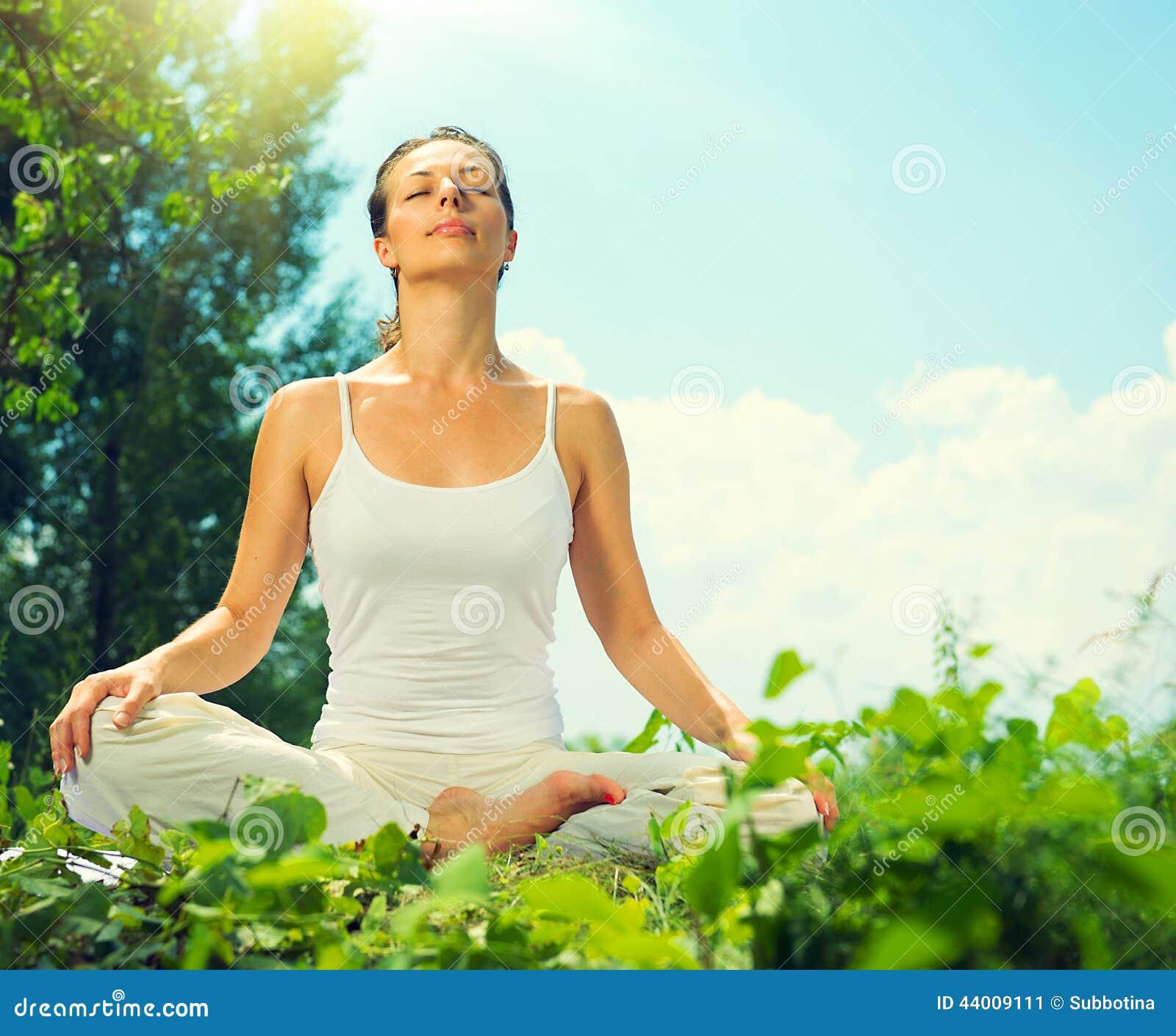 Mujer joven que hace ejercicios de la yoga