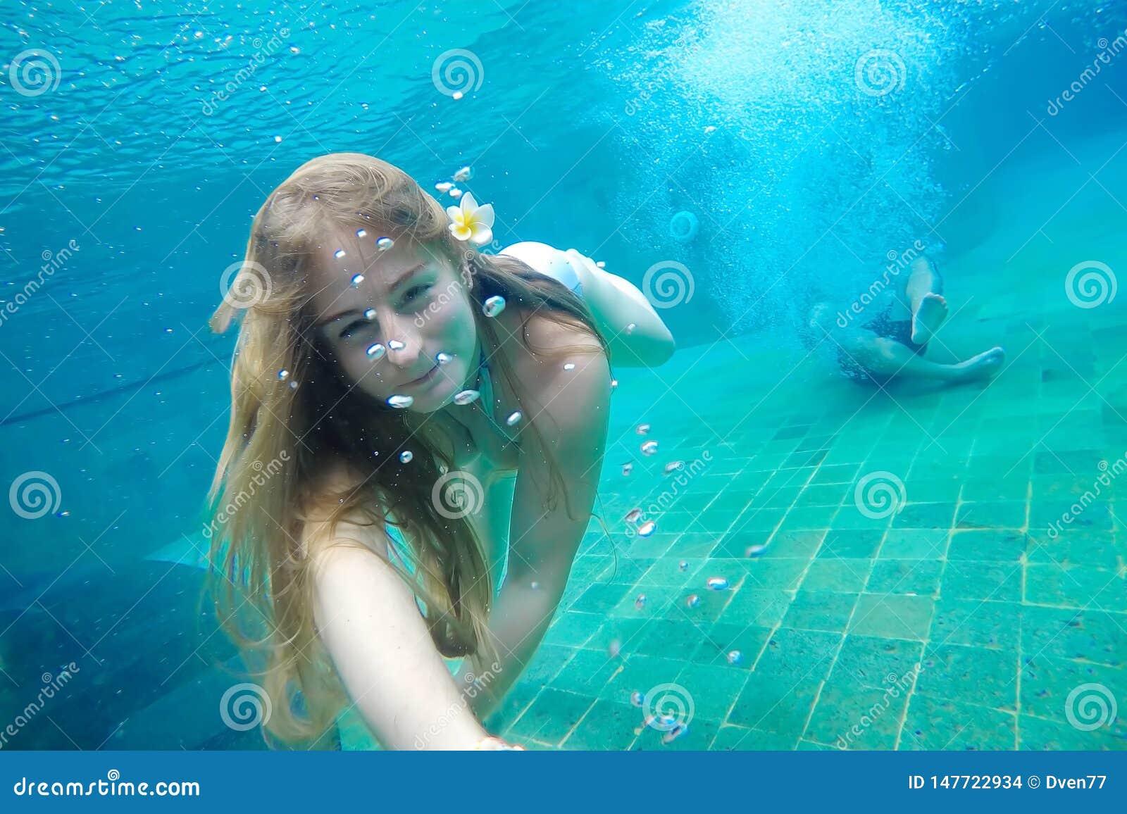 Mujer joven que hace el selfie debajo del agua en la piscina En su pelo es una flor del frangipani Contra el fondo un individuo j