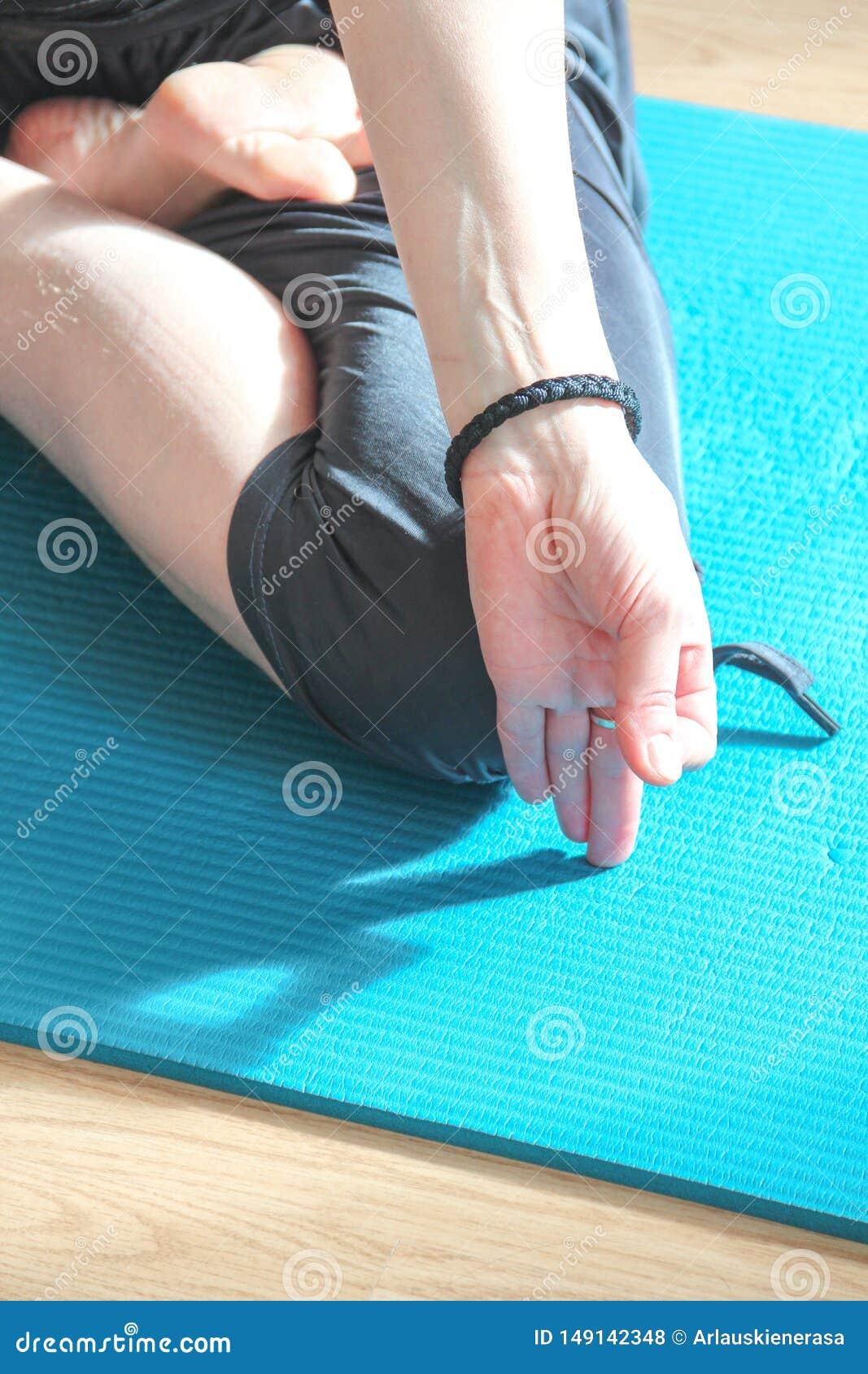 Mujer joven que hace la actitud de la yoga - asana - en casa en una sol