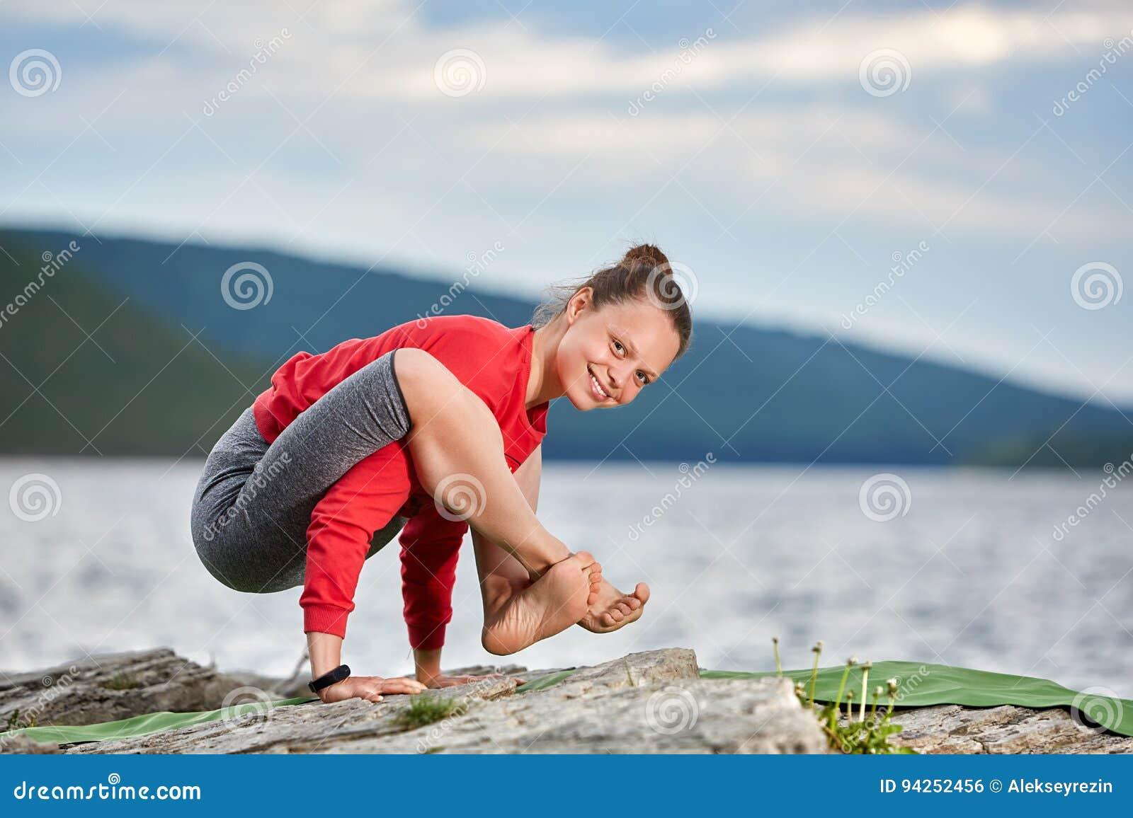 Mujer joven que hace la balanza del brazo de la actitud de la yoga en el río grande cercano de piedra