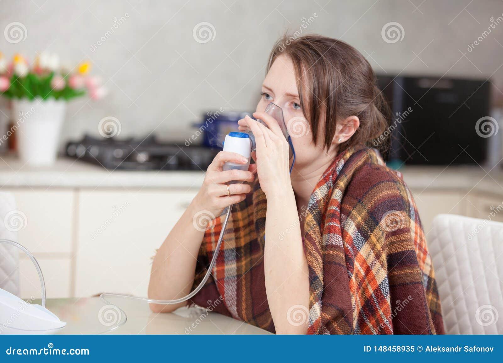 Mujer joven que hace la inhalaci?n con un nebulizador en casa